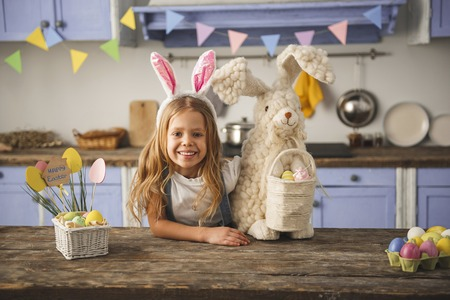 Portrait of laughing kid standing in the cuisine near wooden table and hugging easter bunny. She is wearing hoop with rabbit ears on head. Copy space in right side