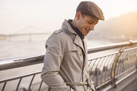 I feel good. Side view profile of cheerful stylish guy is standing on street and looking down with smile. He is holding hands in pockets of his coat