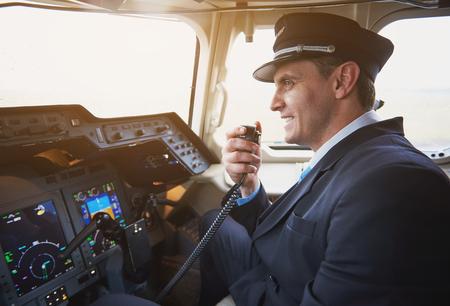 Vista lateral feliz piloto hablando por radio portátil en la cabina del avión. Concepto de conversación y ocupación.