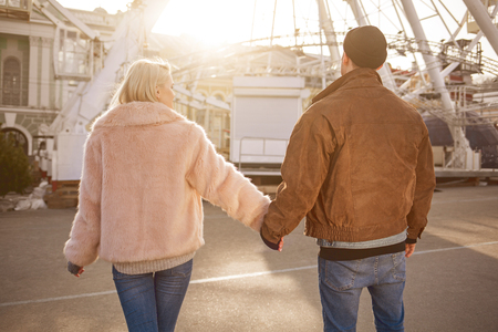 Always together. Back view of loving young couple standing on street in front of ferris wheel. They are holding hands while expressing interest Stock Photo