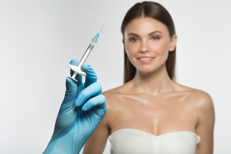 Focus on beautician hand in glove holding syringe with hyaluronic acid. Happy young woman is looking at it and smiling while standing on background. Isolated Zdjęcie Seryjne
