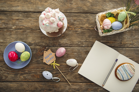 Top view of delicious sugary bread, painted eggs and copybook on the wooden surface