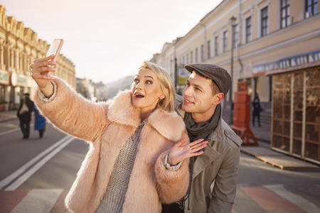 Say cheese. Cheerful young couple making selfie using mobile phone and standing on street. Girl is holding gadget and expressing astonishment Stock Photo
