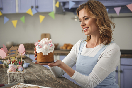 Pleased young woman sitting in decorated cooking room. She is holding and staring at holiday sweet bread Stock Photo