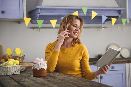 Joyful lady sitting in kitchen and looking at opened notebook she is holding while talking by phone. Basket with painted eggs and glazed easter cake are standing on table. Colorful flags on background