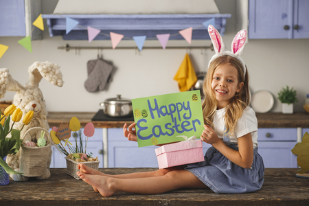 Full length portrait of content child relaxing in the decorated kitchen. She is holding poster with the inscription of happy easter Reklamní fotografie