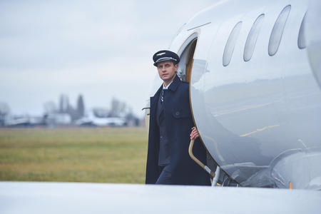 Portrait of pensive young pilot descending from aircraft. Occupation concept. Copy space