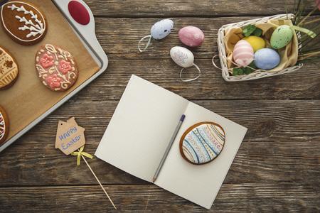 イースターの装飾のクローズアップトップビューとペンと卵の形のクッキーを持つエクササイズブックを開きました