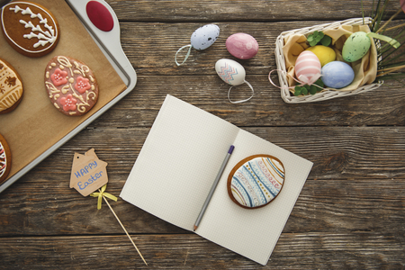 Top view close up of easter decorations and opened exercise book with pen and egg shaped cookie on it 版權商用圖片 - 96374198