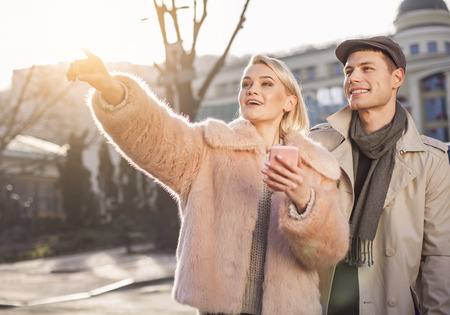 It is amazing. Young positive girl is standing on street with her boyfriend. Female is pointing finger aside and they are expressing interest while looking to that place