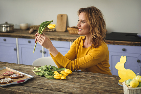 Joyful pretty woman sitting at wooden table and looking at yellow tulip she is holding in hand. Country style kitchen on background