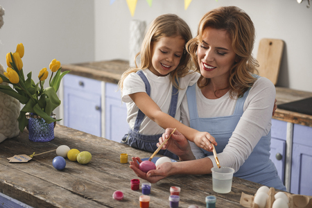 Cheerful mother and kid spending holiday together. They are painting eggs and laughing. Copy space in left side