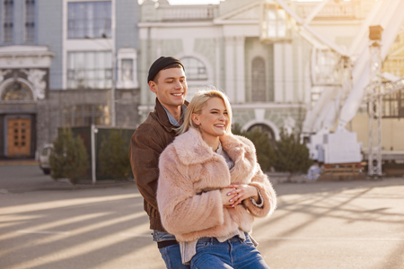Hold me. Cheerful stylish guy is standing from behind and hugging attractive girl. They are smiling while having fun together outdoors