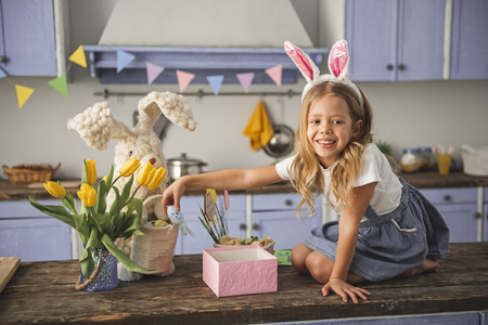 Portrait of smiling girl in a rabbit costume playing with colored egg on the kitchen wooden surface