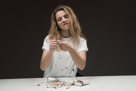 Waist up portrait of angry blonde woman sitting at table with pile of cigarettes and squashing several of them with hands. Isolated on background
