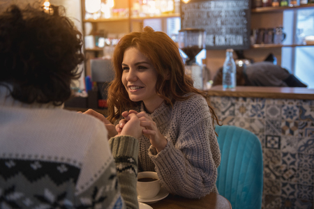 Portrait of glad young red-haired girl looking at her boyfriend with love and smiling. They are touching hands and smiling while sitting in cafe