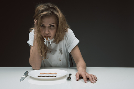 Portrait of displeased lady looking at camera with disgusting face while holding bunch of cigarettes in mouth. Plate with coffin nails on the table. Copy space in right side. Isolated on background