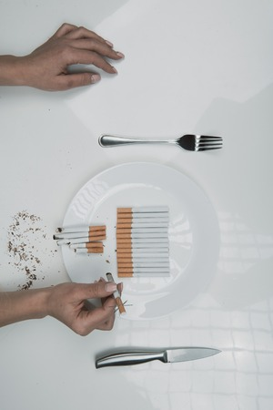 Top view of girl arms with spiny ciggy and dish filled with cigarettes on the table. Close up