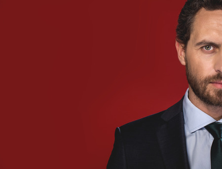 Half face of pensive bearded young man is standing and looking at camera seriously. Isolated on red background. Copy space in the left side