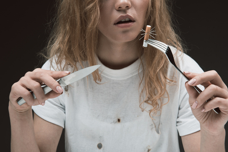 Peaceful woman holding knife and fork with prickly cigarette end on it. Isolated on background 스톡 콘텐츠
