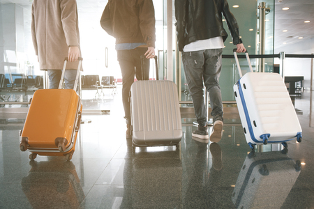 Three male friends keeping luggages while going in airport. Trip concept Stock Photo