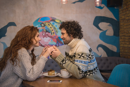 I love you. Affectionate young man and woman are looking at each other eyes with love. They are holding hands while sitting at table in restaurant