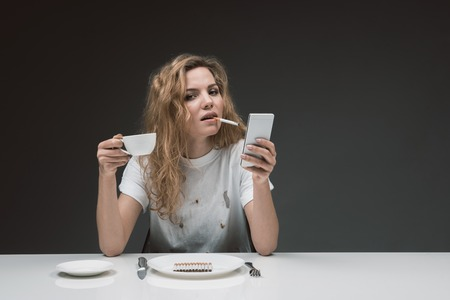 Portrait of confident female sitting and fuming. She is holding beverage and gadget in hands. Copy space in right side. Isolated on background Stock Photo