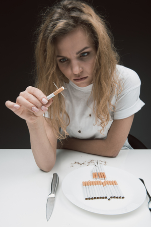Portrait of down girl sitting and looking at prickly ciggy. Plate with rollups standing on table. Isolated on background
