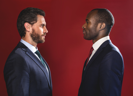 Rivalry concept. Profile of two guys are standing opposite and looking at each other defiantly. Isolated on red background Stock Photo
