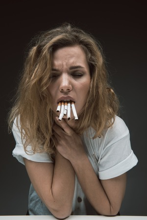 Portrait of upset woman with mouth filled with cigarettes holding hands on neck. Her eyes are closed. Isolated on background