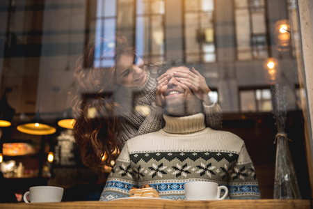 Guess who it is. Cheerful young woman is closing male eyes secretly. Man is sitting at table near window and laughing with excitement