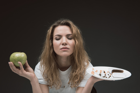 Portrait of concentrated blonde female with eyes closed holding apple on one hand and cigarettes on other. Isolated on background