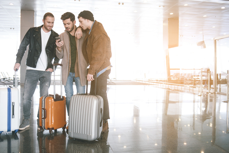 Interested comrades looking at mobile while keeping luggages in airport. Copy space. Journey concept Фото со стока