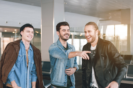 Portrait of laughing comrades telling together. Cheerful man pointing finger in hall. Fun and friendship concept Фото со стока