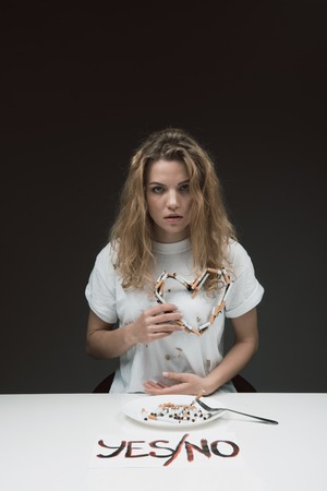 Waist up portrait of concentrated woman looking at camera and holding heart made of cigarettes. She is sitting at the table with inscription yes no and plate with ciggies standing on it. Isolated on background Imagens