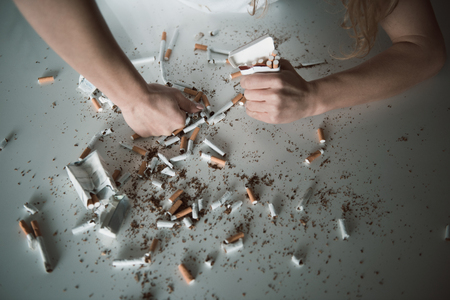 Female hand smashing cigarettes on table with fist, other hand is squeezing pack with cigars. Close up top view Stock Photo