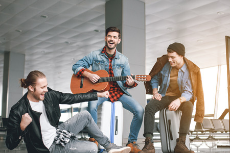 Cheerful man performing melody with musical instrument while sitting near friends in airport. Inspiration concept