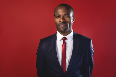 Unshakable decision. Portrait of young african entrepreneur in suit is standing and looking at camera seriously. Isolated on red background