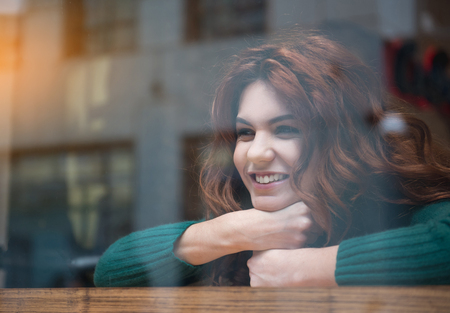 Portrait of happy red-haired young woman looking over the window and laughing. She is resting while leaning head on table. Copy space