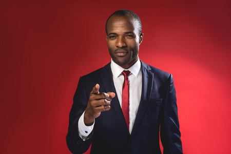 Hey you. Waist-up portrait of serious young african manager is pointing you while standing. Isolated on red background Banco de Imagens