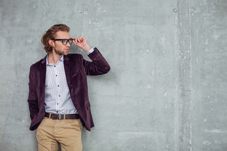 Side view assured bearded male keeping glasses by hand. Self-confidence concept. Copy space