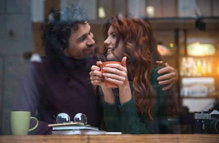 居心地の良いカフェテリアでデートする楽しい若い恋人たち。彼らは愛情と笑顔でお互いを見ています。カップルは熱いお茶を飲んでいます