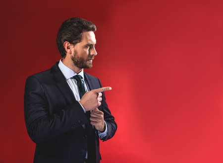 You. Waist-up profile of serious young elegant businessman in suit is standing and pointing finger aside. Isolated on red background and copy space in the right side Banco de Imagens - 96749292