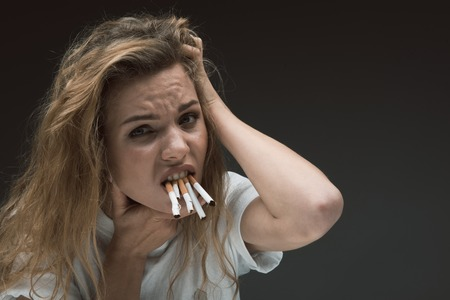 Portrait of depressed woman holding many ciggies with her teeth and looking at camera with disgust. Copy space in right side. Isolated on background