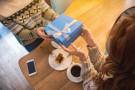This is for you. Top view close up of male hands giving blue present box to loving woman. Lovers are sitting at table in cafeteria Foto de archivo - 96749432