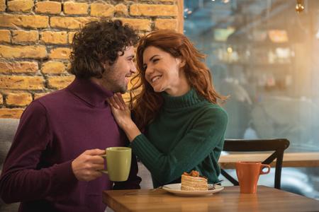 幸せな若い男女がいちゃついて微笑んでいる。居心地の良いカフェテリアのテーブルに座ってコーヒーを飲んでいる。