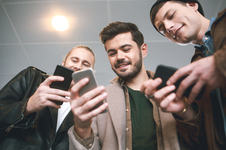 Low angle cheerful male comrades using mobile while keeping them in hands. Technology concept