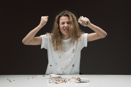 Waist up portrait of disgruntled female sitting at table with pile of cigarettes and squeezing pack in hand with anger. Isolated on background Banco de Imagens