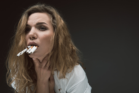 Sad woman touching her neck while having vomiting reflex from tobacco in her mouth. Copy space in right side. Isolated on background