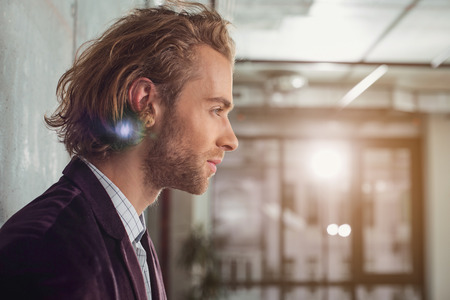 Side view pensive unshaven businessman situating in office. Reverie concept. Copy space